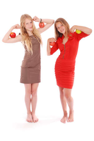 Two girls holding apples on her biceps. Isolated on white.