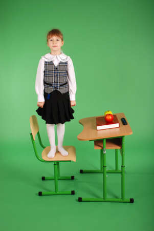 two persons only: Girl in school uniform standing on a chair isolated on a green background