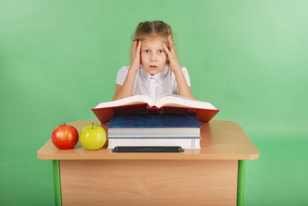 Education, people, children and school concept - young school girl sitting at table with book over green Stock Photo