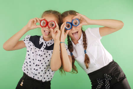 Two beautiful school girl holding two insulating tape on eyes for radiant look on green
