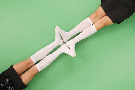 stocking feet: Two girls in knee-length socks isolated on green background