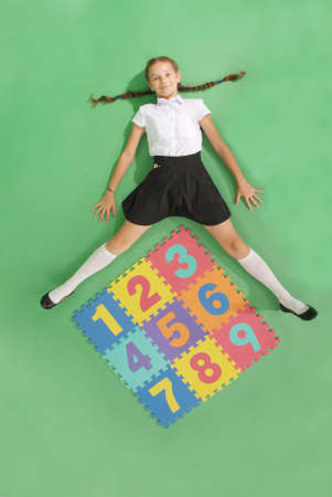 seven persons: School girl is lies in front of a rug with numbers on green