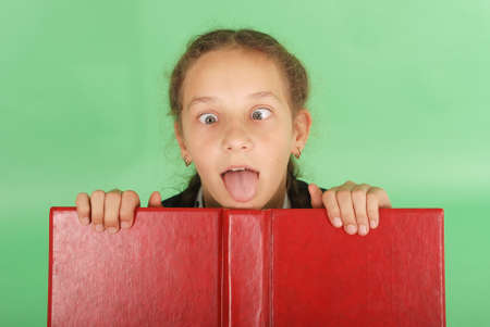 peeping: Beautiful school girl peeping from behind her red book. Pull a face. Isolated on green