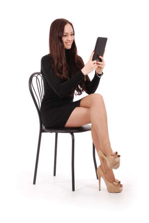 Girl sits on a chair and looking at tablet pc isolated on white