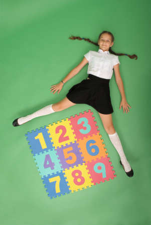 School girl is lies in front of a rug with numbers on green