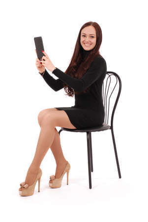 Girl sits on a chair and holding a tablet computer isolated on white Stock Photo