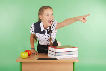 Girl in a school uniform sitting at a desk and points isolated on green