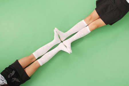 pies bonitos: Dos niñas en calcetines hasta la rodilla aislados en el fondo verde