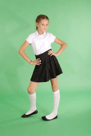 Belle jeune fille en uniforme scolaire isolé sur le vert