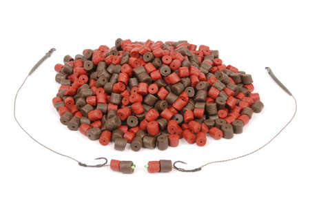 Fishing bait with hook and brown with red pre-drilled halibut pellets for carp fishing isolated on white background with soft shadow Stock Photo