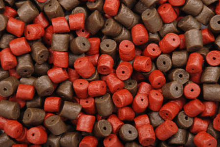 Brown with red pre-drilled halibut pellets for carp fishing  background Stock Photo