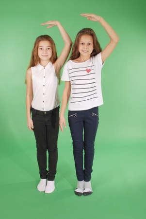 Dos niñas de la escuela toman de las manos sobre la cabeza y la medición de su crecimiento aislado en verde