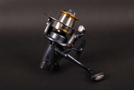 Reel for fishing rods, close up on the black background