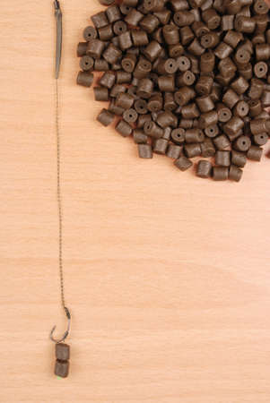 drilled: Fishing bait with hook and brown pre-drilled halibut pellets for carp fishing isolated on wood background with soft shadow Stock Photo
