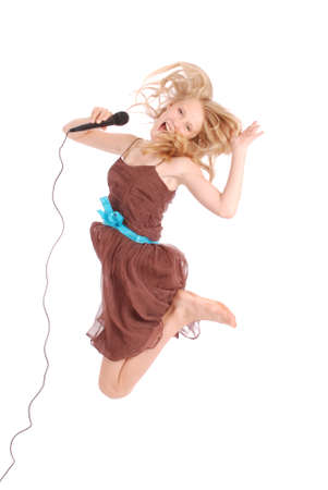 an entertainer: Happy young beautiful teenage girl jumping and singing with microphone isolated on white background Stock Photo