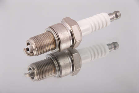 One new spark plugs on a mirror background Stock Photo