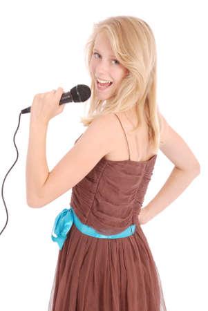 白い背景で隔離のマイクを使って歌う幸せな若い美しい女の子 写真素材