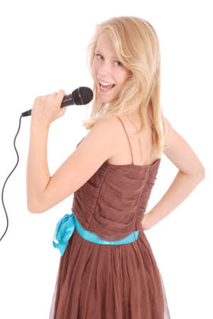 Happy young beautiful girl singing with microphone isolated on white background Фото со стока