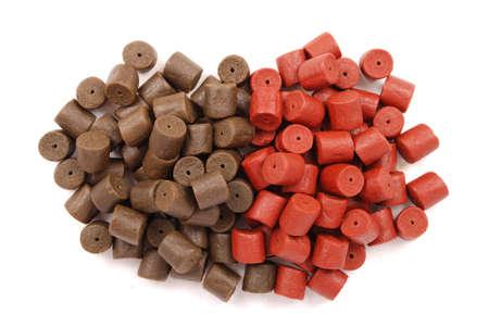 biomasa: Brown con rojo pre-perforado pellets de halibut para la pesca de la carpa aisladas sobre fondo blanco con sombra suave Foto de archivo