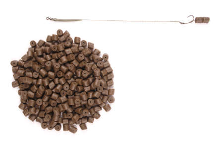 forage fish: Fishing bait with hook and brown pre-drilled halibut pellets for carp fishing isolated on white background with soft shadow Stock Photo