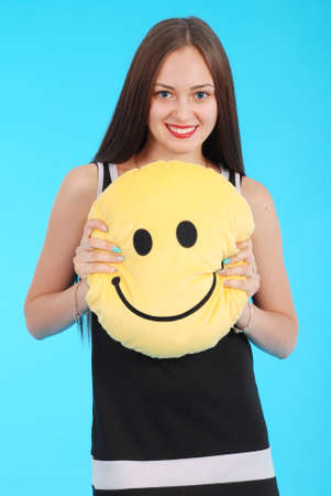 tenager: Cheerful young girl is holding a smiley face pillow are standing against the blue background