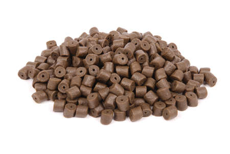 forage fish: Brown pre-drilled halibut pellets for carp fishing isolated on white background with soft shadow Stock Photo