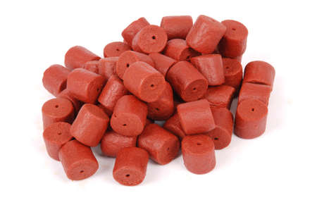drilled: Red pre-drilled halibut pellets for carp fishing isolated on white background with soft shadow