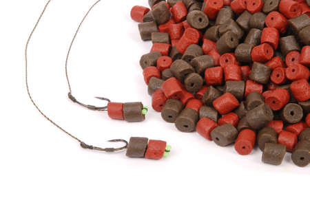 biomasa: Fishing bait with hook and brown with red pre-drilled halibut pellets for carp fishing isolated on white background with soft shadow Foto de archivo