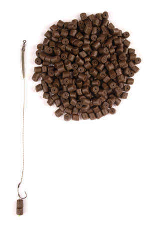 drilled: Fishing bait with hook and brown pre-drilled halibut pellets for carp fishing isolated on white background with soft shadow Stock Photo