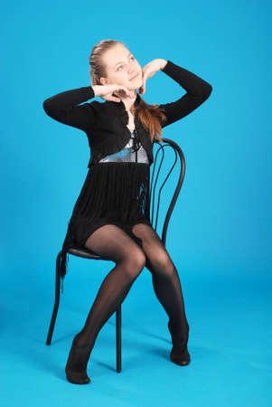 Het vrolijke jonge meisje zit op een stoel tegen de blauwe achtergrond Stockfoto