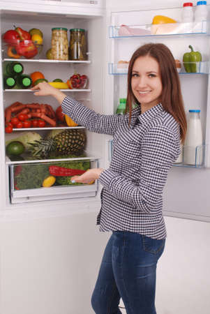 Satisfied housewife near filled fridge. Beautiful young girl near the fridge.