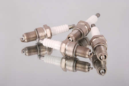 Four new spark plugs on a mirror background Stock Photo