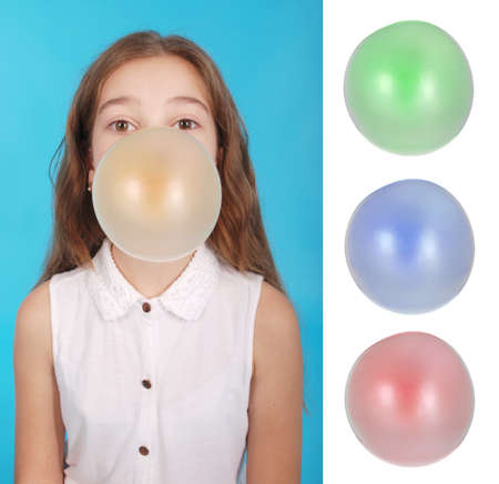 Girl blowing a big bubble gum bubble isolated on blue. Many varieties of gum color for your Projects Stock Photo