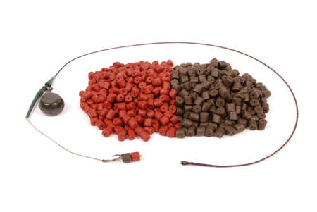 drilled: Fishing bait with hook and brown with red pre-drilled halibut pellets for carp fishing isolated on white background with soft shadow Stock Photo