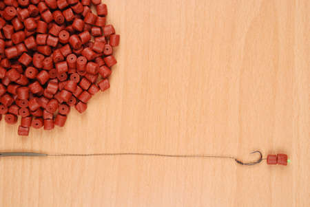 forage fish: Fishing bait with hook and red pre-drilled halibut pellets for carp fishing isolated on wood background with soft shadow