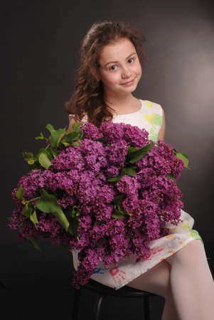 Portrait of adorable smiling girl sitting on a chair with a bouquet of flowers,  isolated on a back background