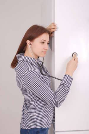 refrigerator: Young woman listening closed fridge with stethoscope to breaks it Stock Photo