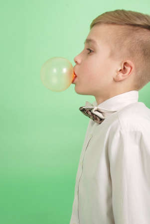 masticate: Boy blowing a bubblegum bubble isolated on green
