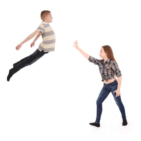 levitate: Girl keeps the boy in will in the air. Levitation with the power of thought. Isolated on white Stock Photo