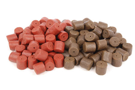drilled: Brown with red pre-drilled halibut pellets for carp fishing isolated on white background with soft shadow
