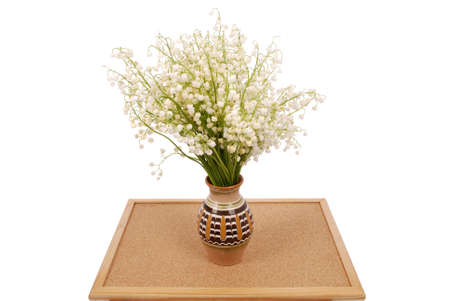 Bouquet lily of the valley in a pot on the wood stand isolated on white background with soft shadow Stock Photo