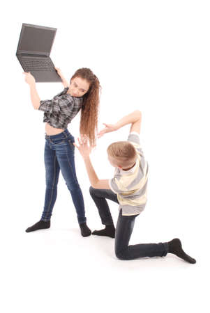 Boy and girl fighting over a laptop, isolated on white Stock Photo