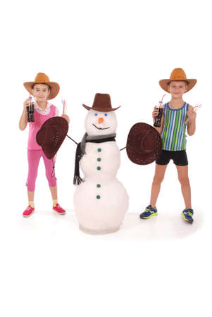 Cute boy and girl holding a cola bottle near a snowman with scarf and hat on white background Stock Photo