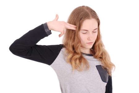 Young teen girl shoots herself in the head with finger gun gesture. Girl holding imaginary gun on her head. Human emotions face expressions. Isolated on white Stock Photo