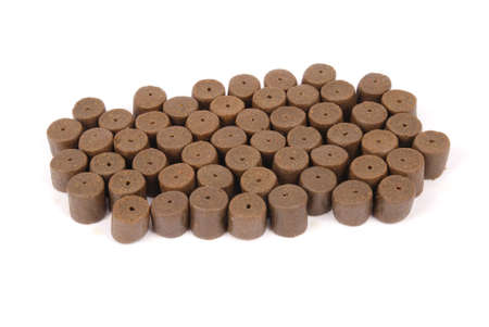 Brown pre-drilled halibut pellets for carp fishing isolated on white background with soft shadow Stock Photo