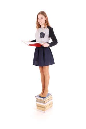L'éducation, les gens, l'adolescent et le concept d'école - écolière adolescente debout sur une pile de livres. Isolé sur blanc