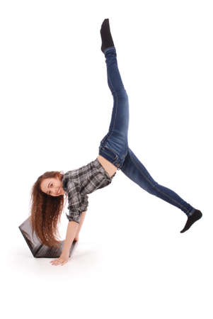 Girl doing acrobatic stunt and using laptop isolated on a white