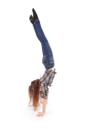 Girl in jeans doing acrobatic stunt isolated on white