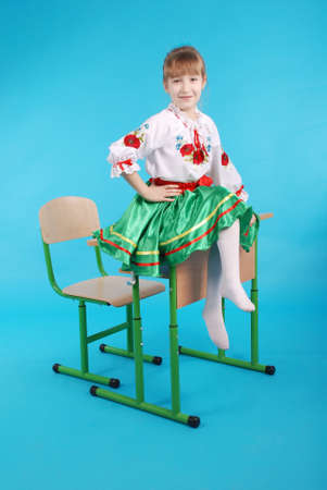 Young girl with light hair in Ukrainian embroidery sitting on school desk isolated on blue backround