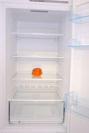One pepper in open empty refrigerator. Weight loss diet concept. Foto de archivo